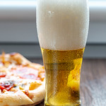 Glass of beer with foam and pizza on the table thumbnail