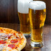 Two glasses of cold beer with pizza