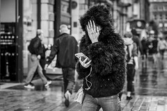The All Seeing Eye (Leanne Boulton) Tags: urban street candid portrait portraiture streetphotography candidstreetphotography candidportrait streetportrait eyecontact candideyecontact streetlife woman female girl face eyes expression emotion mood hiding hand gesture nails fingernails fur furry coat hood rain raining shower water summer tone texture detail depthoffield bokeh naturallight outdoor light shade city scene human life living humanity society culture lifestyle people canon canon5dmkiii 70mm ef2470mmf28liiusm black white blackwhite bw mono blackandwhite monochrome glasgow scotland uk