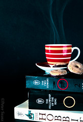 Afternoon chill (Peter Szasz) Tags: colourful calm canon canon80d 80d 2470mm 2470 telephoto orange object still stilllife afternoon black dark shadows shade indoors bright yellow circular circle ring brown white red cookie biscuit book read reading tolkien jrr hobbit lordoftherings lord rings blackback background chill peaceful creative product programme cup saucer coffee cafe steam smoke wavy