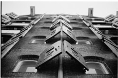Wide open (Elios.k) Tags: horizontal outdoors nopeople building architecture lookingup exterior windows open shutters casementwindows wooden old channel streetphotography dof depthoffield focusonforeground backgroundblur bokeh blackandwhite brick wall perspective pattern abstract bw mono monochrome travel travelling may 2018 canon camera photography amsterdam netherlands nederland europe film analoguephotography scannedfilm kodaktrix400 analogfilm grain contrast canona1 a1 analogcamera