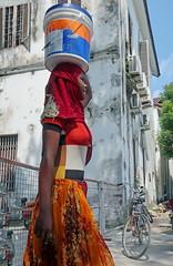 Working Construction - Stonetown, Zanzibar (TravelsWithDan) Tags: candid streetportrait constructionworker youngwoman carryingonherhead muslim covered colorful urban city stonetown zanzibar tanzania africa canong9x ngc