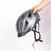 Hand holding black bike helmet