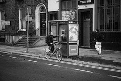 Need it Right Now (Tom Levold (www.levold.de/photosphere)) Tags: dublin fuji xpro2 xf35mm sw street bw youngwoman jungefrau cyclist radfahrerin xf18135mm