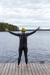 Man from behind with extended arms, in neoprene suit , swimming cap and diving goggles on a wooden jetty at Lake Päijänne in Finland (verchmarco) Tags: im703finland finnland ironman sports lahti visitlahti travel finland water wasser people menschen nature natur recreation erholung summer sommer fun spas outdoors drausen one ein man mann sea meer leisure freizeit reise woman frau relaxation entspannung sky himmel young jung exercise übung active aktiv adult erwachsene sport sport2019 2020 2021 2022 2023 2024 2025 2026 2027 2028 2029 2030 child dawn colours farm kodak truck outside ciel nikkor design