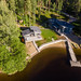Man on a wooden jetty takes Ariel shot  of the guest house Villa Jolla at Finland's longest lake Päijänne, with canoes and nordic forest in the background