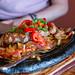 Rindfleisch-Fajitas mit gegrilltem Rinderfilet, in Scheiben geschnitten, Gemüse, Kräutern und Zwiebeln, auf einem schwarzen Steinteller