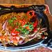 Flatlay von gegrillten Fajitas aus Rinderlende, mit Paprika, grünen Kräutern und Zwiebeln, auf rustikalem Holztisch-Ambiente