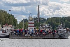 Sportbegeisterte Zuschauer stehen und sitzen beim Leuchtturm am Hafen von Lahti, Finnland & blicken auf Ironman-Teilnehmern beim Schwimmwettkampf