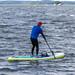 Mann benutzt beim Stand-up-Paddling die Fußschlaufe und paddelt über den Vesijärvi-See in Finnland