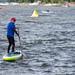 Wassersportler auf einem Stand-up-Paddleboard am Rand des Schwimmwettbewerbs für den Ironman 70.3 beobachtet die Triathleten