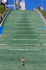 Runner in sports clothes runs up the green ski jump Salpausselkä in Lahti, for her endurance training