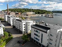 """Luftbild zeigt Mehrfamilienhäuser am Hafen von Lahti, mit altem Hafengebäude im Hintergrund & Konzert-und Kongresshalle """"Sibelius Talo"""" am Vesijärvisee"""