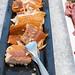 Portionierter Fisch am Hotelbüfett, für ein ausgewogenes Essen, angerichtet auf einem schwarzen Tablett und auf Eiswürfeln gekühlt