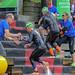 Triathleten rennen nach dem Schwimmwettkampf eine Holztreppe hoch