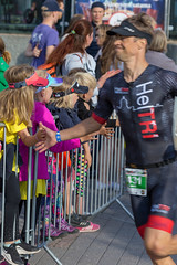 Sports enthusiasts and children behind security barriers high-five Ironman participants and runners on the marathon course in Lahti, Finland
