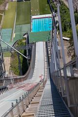 Ansicht von oben auf die Skisprungschanze Salpausselkä mit dem besonderen Außenschwimmbad im Sportzenrum von Lahti, Finnland