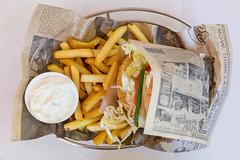 Vegetarischer Burger von Bus Burger in altem Vintage-Zeitungspapier gewickelt, mit Ziegenkäse-Patty, Senfsauce, cremigem Dip und Pommes Frites