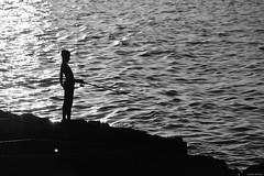 Joven pescador en el Malecón (La Habana, Cuba). (Carlos Arriero) Tags: lahabana cuba pescador fisherman blackandwhite bw blancoynegro bn carlosarriero contraste contrast contraluz viajar travel nikon d800e 70200mmf28 agua water mar sea