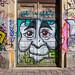 Graffiti als Streetart, auf einer Hausfassade und Holztür in München, Deutschland