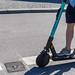Mann fährt auf einem E-Scooter auf einer Straße in München, um die Verkehrswende zu unterstützen