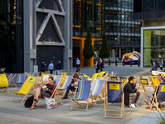 Sitting Pretty (Steve Taylor (Photography)) Tags: aviva deckchairs avivasthelensbuilding avivatower stmaryaxe city london relaxing reading book chatting texting sitting support architecture sculpture blue yellow people uk gb england greatbritain unitedkingdom stripes