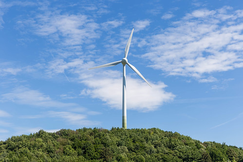 Symbol of renewable energy with a single wind power plant on