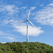 Symbol of renewable energy with a single wind power plant on a mountain, in front of a blue sky, to convert wind energy into electrical energy