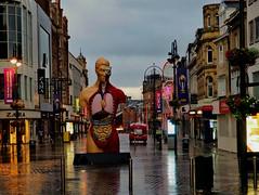 Watchful eye, wet skies (oneofmanybills) Tags: damien hirst leeds rain streetlights city reflections sculpture body human art eye watching
