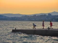sunset afterglow - Podstrana, Croatia (jeffglobalwanderer) Tags: split croatia podstrana beachlife pier dock water adriaticsea sunsetglow coastline childrenplaying watchingsunset sunset orangesky