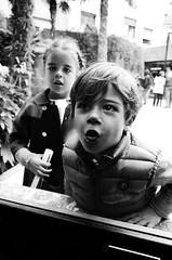 (Russell Siu) Tags: bw street candid monochrome grey kids children playing boy girl stare spanish barcelona spain
