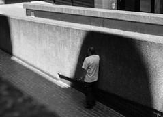 Shade (Spannarama) Tags: blackandwhite sunlight sunshine shadow lightanddark lightandshade concrete wall brutalist architecture modernist textures man standing leaning barbican ramp fannstreet london uk vintagelens helios442 58mm filmlens