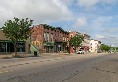 Buildings — Circleville, Ohio (Pythaglio) Tags: street ohio brick cars clouds buildings unitedstatesofamerica structures historic sidewalk commercial storefronts ornate twostory brackets cornice italianate circleville hoodmolds friezewindows