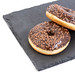 Chocolate Donuts on the black stone tray with copy space