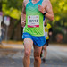 Nahaufnahme eines Marathonläufers beim Joggen auf abgesperrter Straße, während des Köln Marathon