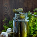 Glass jar with pickles, dill and garlic on wooden background