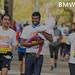 Marathon participant in jeans running the BMW Frankfurt Marathon with a child on his arm