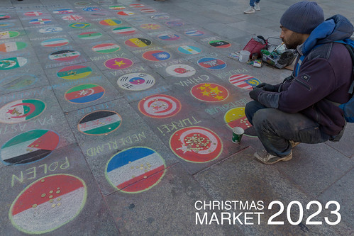 Urban street artist collects money and shows all kind of country flags, next to picture title Christmas Market 2023