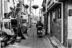 Mess-up (Go-tea 郭天) Tags: pékin républiquepopulairedechine beijing hutong ancient old history historical historic traditional tradition construction buildings narrow alley pavement motorbike motorcycle ride riding rider mouvement stairs mess messy cny cold winter sun sunny shadow electric electricity lines box alone lonely man leaving back backside street urban city outside outdoor people candid bw bnw black white blackwhite blackandwhite monochrome naturallight natural light asia asian china chinese canon eos 100d 24mm prime transport transportation