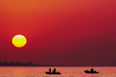 Fishing at sunrise (Fnikos) Tags: sea seascape water sky cielo skyscape skyline mountain bay reflection color colour colores colours colors shadow shadows sun sol sole sunrise salidadelsol amanecer dawn coast fishing pesca boat motorboat people outside outdoor