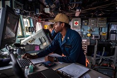 A Sailor checks the ship's hourly position on the voyage management system in the ship's bridge.