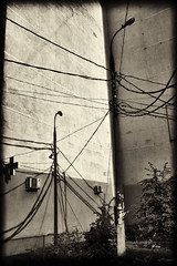 abstract with wires and shadows (Pomo photos) Tags: abstract abandoned evening wire noir surrealism pillar surreal cable pole wires fujifilm abstraction x100t fujifilmx100t street city urban blackandwhite bw building tree monochrome wall sepia architecture mono blackwhite mood cityscape geometry decay details expressionism