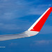 Wing of the plane AirAsia with red winglets in flight in blue sky    XOKA0058bs
