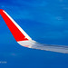 Wing of the plane AirAsia with red winglets in flight in blue sky     XOKA0058b2s