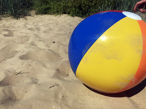 Coloured beach ball in the sand. Summer stock photo.