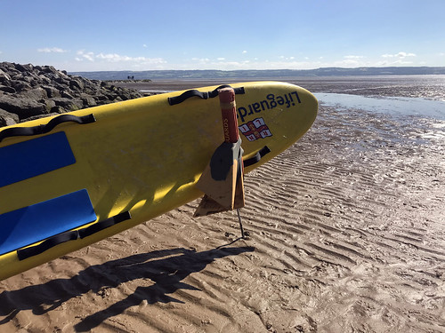 Lifesaving surfboard at the beach by a low tide, free to use beach stock photo