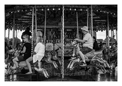 FILM - Riders (fishyfish_arcade) Tags: 35mm analogphotography bw blackwhite blackandwhite filmphotography filmisnotdead hp5 istillshootfilm monochrome nikkor2880f3556afd nikonf80 sheffieldsteamrally analogcamera compact film ilford mono carousel streetphotography