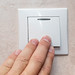 Man's hand with fingers on light switch, about to turn off the lights