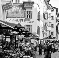 Bolzano street market (@WineAlchemy1) Tags: street market viamuseo museumstrasse bolzano bozen altoadige südtirol southtyrol italy blackandwhite blancoynegro nerosubianco noiretblanc torgglhaus casaaltorchio piazzadellaherbe