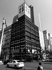 Motionless Crab Building 2 (sjrankin) Tags: 10july2019 hokkaido japan sapporo downtown buildings grayscale restaurant crab road intersection cars people